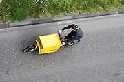 In Nijmegen fietst een medewerker van DHL op een tweewielige bakfiets door de stad. Bakfietsen worden in heel Europa steeds vaker ingezet, zowel door particulieren als bedrijven. Het is een duurzame vorm van transport en biedt veel voordelen.<br /> <br /> In Nijmegen an employee of DHL is cycling on a two-wheel cargo bike in the city center. Cargo bikes are increasingly being deployed across Europe, both individuals and businesses. It is a sustainable form of transport and offers many advantages.
