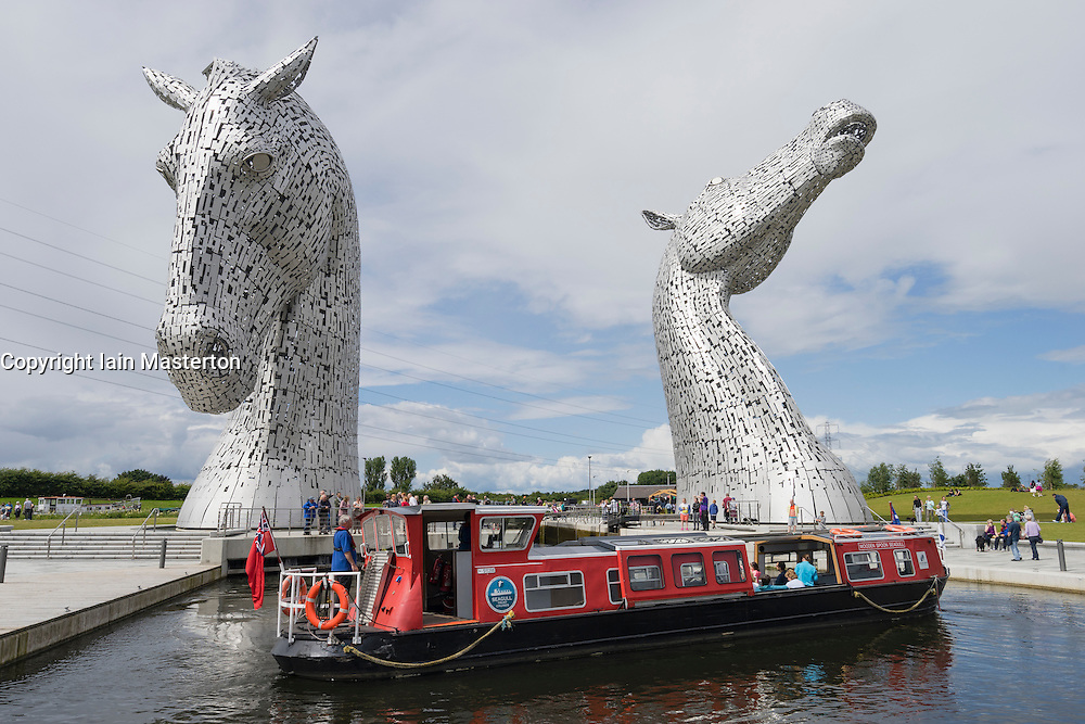 The Kelpies sculpture of two horses crossing Forth and Clyde Canal and tourist canal boat at The Helix Park near Falkirk, Scotland