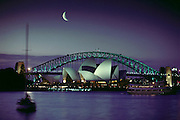 Sydney Opera House and bridge, with quarter moon, in Sydney Harbor. Sydney, Australia.