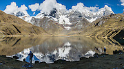 Cordillera Huayhuash reflects in Carhuacocha lake (13,600 feet) in the Andes Mountains, Peru, South America. Peaks from left to right are: Siula Grande, Yerupaja Grande (6635 m or 21,770 ft, highest point in the Amazon watershed), Yerupaja Chico, and Mount Jirishanca (Icy Beak of the Hummingbird). Day 3 of 9 days trekking around the Cordillera Huayhuash. This panorama was stitched from 4 overlapping photos.