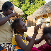 Young ladies of Koumbadiouma braid each other's hair, getting ready for Islamic New Year. Kolda, Senegal.