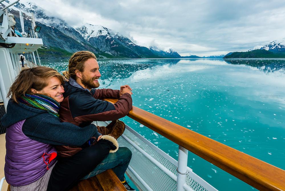 Couple enjoy the scenery of Glacier Bay National Park (Grand Pacific Glacier in background) aboard the Un-Cruise ship Wilderness Explorer, southeast Alaska USA.