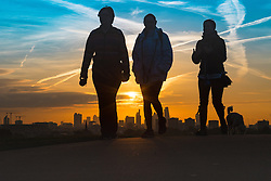 Primrose Hill, London, October 28th 2016. Three friends walk their dogs on Primrose Hill as the sun rises over London's skyline.