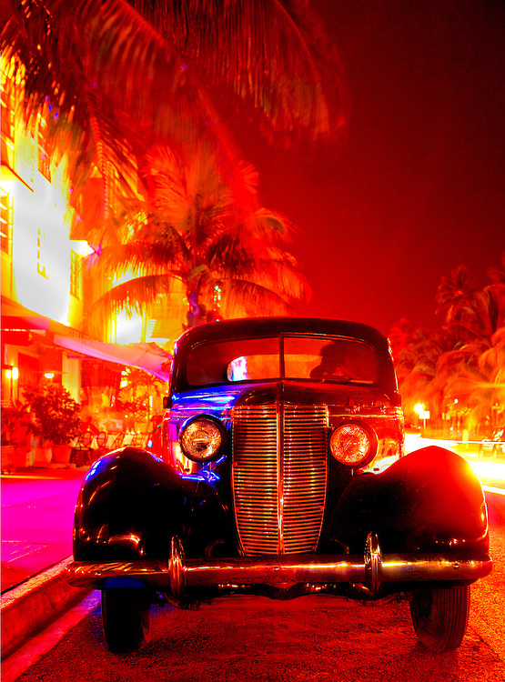 Palm trees and neon-lit, Art Deco hotels line Miami Beach's Ocean Drive in historic South Beach. Car is a 1937 Nash Lafayette. At left is the Park Central Hotel, also designed in 1937.
