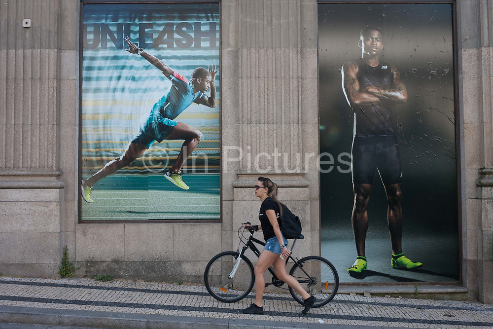 A young woman pushes her bike up a steep hill, beneath the posters of athletes advertising sports clothing using the word Unleash as its slogan, on 20th July, in Porto, Portugal.
