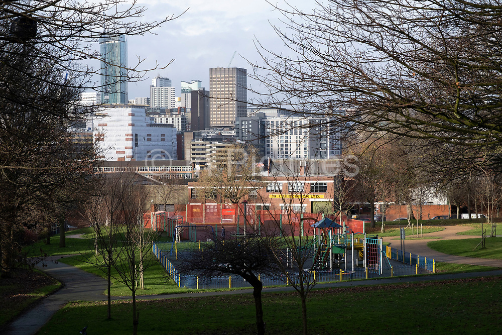 View towards the city over a childrens play area in the inner city area of Highgate on 14th December 2020 in Birmingham, United Kingdom. Following the Big City Plan of February 2008, Highgate is now a district of Birmingham City Centre, and has a reputation as a generally run down area.