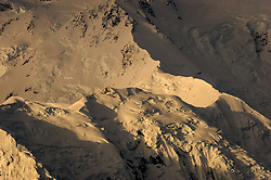 """Denali (Athabaskan for """"The High One"""") basks in morning light at sunrise in Denali National Park and Preserve in Alaska. The snow and glacier covered mountain, part of the Alaska Range soars to a height of 20,310 feet. Denali is the tallest mountain on the North American continent. Although Mt. Everest is higher, the vertical rise of Denali is greater. This view is a small detail from the north slopes of the mountain seen from Wonder Lake."""