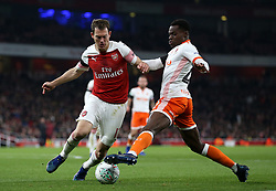 Arsenal's Stephan Lichtsteiner (left) and Blackpool's Mark Bola battle for the ball during the Carabao Cup, Fourth Round match at the Emirates Stadium, London.