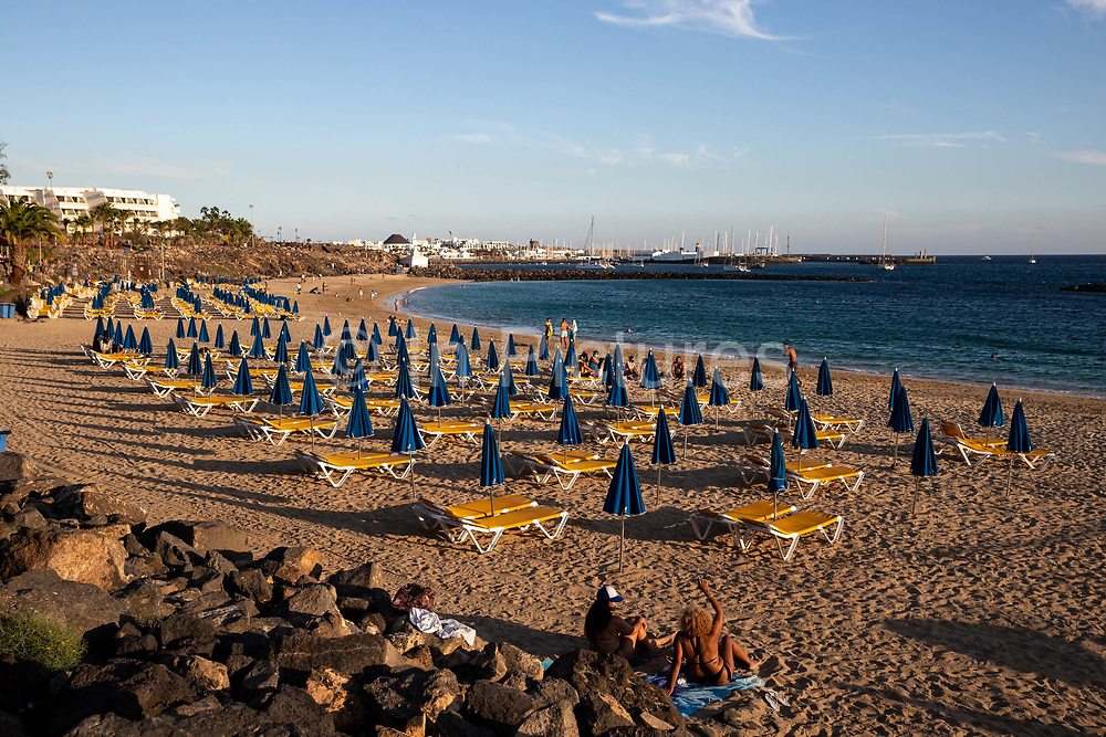 A few holiday makers sit and walk in the sun on the beach at Playa Dorada in Lanzarote, Spain on 22nd November 2020. Beaches and resorts across the island are nearly deserted since tourism plummeted due to Covid restrictions elsewhere in Europe. Although the Canary Islands have been relatively unscathed by the virus, with 155 lives lost from 2.1 million residents, the region is heavily dependent on tourism and locals are hoping that numbers recover as lockdown measures ease and vaccines potentially reduce the numbers of infections.