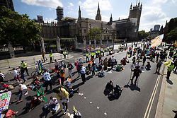 © Licensed to London News Pictures. 01/09/2020. London, UK. A small group of Extinction Rebellion (XR) environmental campaign protesters sit in front of Parliament. XR plan to peacefully disrupt the UK Parliament with actions planned over two weeks, until MP's back the Climate and Ecological Emergency Bill and prepare for crisis with a National Citizens' Assembly. Photo credit: Peter Macdiarmid/LNP