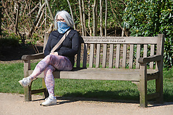 ©Licensed to London News Pictures 23/03/2020<br /> Tunbridge Wells, UK. A lady wearing a mask over her face while sitting on a bench. A very quiet Dunorlan park in Royal Tunbridge Wells, Kent this afternoon as people seem to be following the Coronavirus advice of Social distancing. Photo credit: Grant Falvey/LNP