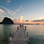 Romantic table for two on wharf overlooks cape at sunset, Palawan, Philippines