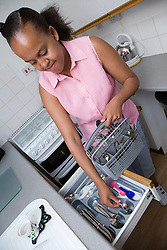 Young woman putting cutlery into a drawer from dish washer basket,