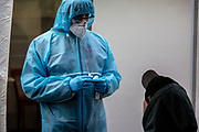 Medical personnel staff member performs a covid antigen rapid swab tests on a person at a covid-19 test station outside the Kitkat night club in Berlin, Germany, December 13, 2020. Berlin's world famous KitKatClub has initiated a fast covid-19 tests operation in its premises People are able to set an online appointment and arrive to have a covid antigen rapid swab test in what was reported by local media outlet as the lowest price in the German capital. The club itself is closed since early 2020 due to the health restrictions imposed on cultural venues in Germany.