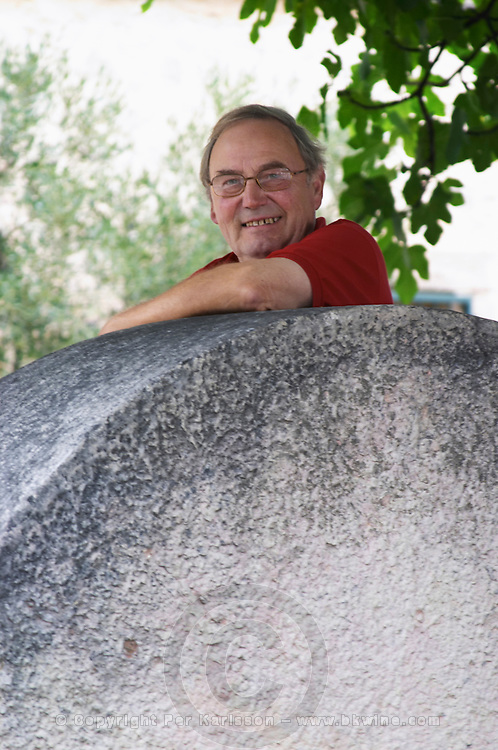 The owner manager Rene Ouenin leaning on an old olive mill stone. Moulin Mas des Barres olive mill, Maussanes les Alpilles, Bouches du Rhone, Provence, France, Europe
