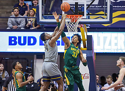 Mar 7, 2020; Morgantown, West Virginia, USA; West Virginia Mountaineers forward Oscar Tshiebwe (34) attempts to dunk over Baylor Bears forward Freddie Gillespie (33) during the first half at WVU Coliseum. Mandatory Credit: Ben Queen-USA TODAY Sports
