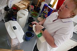 Partially sighted woman making drink,