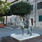 "PITIGLIANO, ITALY - OCTOBER 23: The bronzed sculpture of Villano and his Donkey depicts appreciation for hard working farmers in the Piazza della Repubblica in Pitigliano. Pitigliano is a small village located in Tuscany halfway from Florence and Rome, perched atop a volcanic tufa ridge. Its unmistakable skyline makes it stand out. Pitigliano is a truly unique village in southern Tuscany, in the less-known Maremma district. The town is dubbed ""la citta' di tufo"" for the rock that it not only is built on.<br /> The village is also called ""Little Jerusalem"", not just because it looks ancient and bears a resemblance to that city, but also for the long presence of a Jewish community in the town. Pitigliano, Tuscany, Italy. 23rd October 2017. Photo by Tim Clayton/Corbis via Getty Images)"
