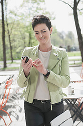 Mature woman text messaging on mobile phone at sidewalk cafe, Bavaria, Germany