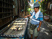 27 AUGUST 2016 - BANGKOK, THAILAND: A grilled banana vendor cooks bananas during a weekend lunch for residents of the Pom Mahakan slum community. The Pom Mahakan community is known for fireworks, fighting cocks and bird cages. Mahakan Fort was built in 1783 during the reign of Siamese King Rama I. It was one of 14 fortresses designed to protect Bangkok from foreign invaders. Only two of the forts are still standing, the others have been torn down. A community developed in the fort when people started building houses and moving into it during the reign of King Rama V (1868-1910). The land was expropriated by Bangkok city government in 1992, but the people living in the fort refused to move. In 2004 courts ruled against the residents and said the city could evict them. The city vowed to start the evictions on Sept 3, 2016, but this week Thai Prime Minister Gen. Prayuth Chan-O-Cha, sided with the residents of the fort and said they should be allowed to stay. Residents are hopeful that the city will accede to the wishes of the Prime Minister and let them stay.       PHOTO BY JACK KURTZ