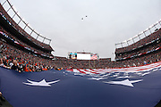 F-18 jets fly over Sports Authority Field at Mile High stadium as a large American flag is displayed on the field as part of pregame festivities before the Denver Broncos NFL week 19 AFC Divisional Playoff football game against the Indianapolis Colts on Sunday, Jan. 11, 2015 in Denver. The Colts won the game 24-13. ©Paul Anthony Spinelli