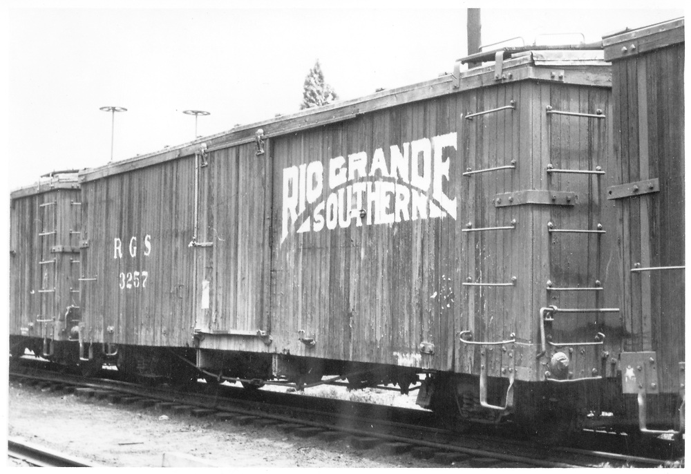 """3/4 view of RGS box car 3257 at Durango.  The Sunrise logo is most likely a hoax, according to Dorman.<br /> RGS  Durango, CO  Taken by Pollack, Tom - ca. 1948<br /> In book """"Durango: Always a Railroad Town (1st ed.)"""" page 172<br /> See RD054-028 for a companion picture."""