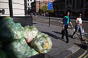 Women walking past a pile of rubbish recycling bags lying on the street outside in Mayfair, London, UK.