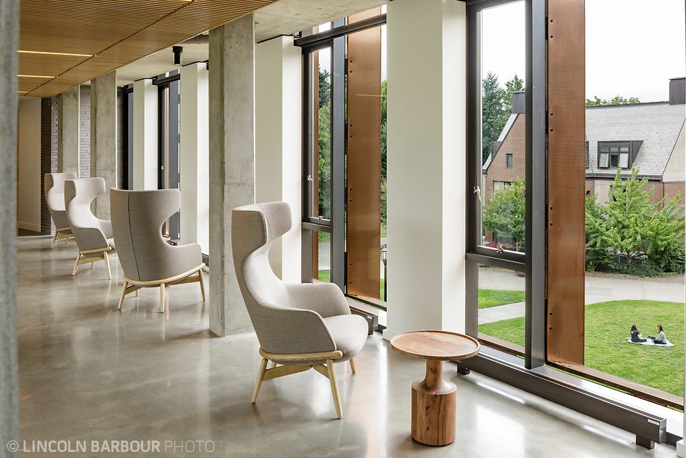 A row of chairs in Trillium Residence Hall at Reed College looking out onto a lawn where two women are hanging out.