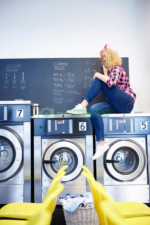 May 24, 2017 - Female laundrette owner sitting on top of washing machine writing on chalkboard (Credit Image: © Image Source via ZUMA Press)