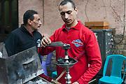 A man prepares a shisha pipe at the Zahrat al-Bustan cafe, Cairo, Egypt