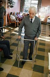 Elderly man walking in residential home using zimmer frame,