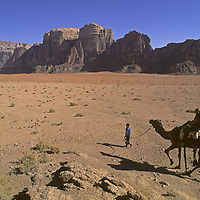 A young Bedouin boy leads rock climber Lisa Gnade on a camel in the Wadi Rum.