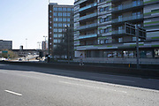 Local atmosphere due to Coronavirus lockdown is felt on a street by street level as streets remain deserted in on St Chads Queensway leading to Aston Expressway, apart from one young woman walking along a wall in the central reservation, as people observe the stay at home advice from the government on 7th April 2020 in Birmingham, England, United Kingdom. This area of main roads through central Birmingham is normally full of cars, but is currently eerily empty of vehicles. Coronavirus or Covid-19 is a new respiratory illness that has not previously been seen in humans. While much or Europe has been placed into lockdown, the UK government has announced more stringent rules as part of their long term strategy, and in particular social distancing.