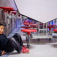 Tyris Chavez waits by himself in the hallway during the Crownpoint Rug Auction at Crownpoint Elementary School April 8.