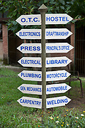 A wooden and metal sign post in an University grounds in Kathmandu, Nepal.  The university mostly offers vocational courses.