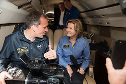 NASA Associate Administrator for the Science Mission Directorate Thomas Zurbuchen explains to acting NASA Administrator Lesa Roe how the spectrograph showing different colors correlate to different elements, such as helium, in the Sun's atmosphere during the solar eclipse Monday, August 21, 2017, from onboard a NASA Armstrong Flight Research Center's Gulfstream III 35,000 feet above the Oregon Coast. A total solar eclipse swept across a narrow portion of the contiguous United States from Lincoln Beach, Oregon to Charleston, South Carolina. Photo Credit: (NASA/Carla Thomas)