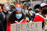 A woman wearing Mauri Tribal Headware and a facemask, holds a placard as she marches through the CBD during a Black Lives Mater rally on 06 June, 2020 in Melbourne, Australia. This event was organised to rally against aboriginal deaths in custody in Australia as well as in unity with protests across the United States following the killing of an unarmed black man George Floyd at the hands of a police officer in Minneapolis, Minnesota. (Photo by Dave Hewison/ Speed Media)