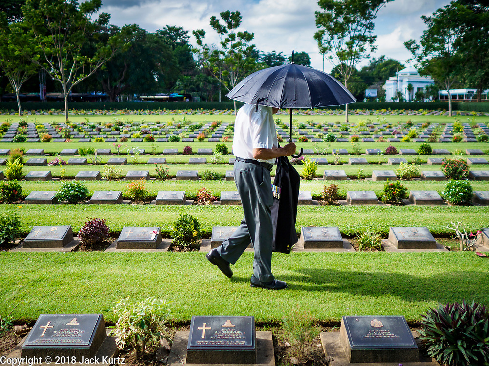 """11 NOVEMBER 2018 - KANCHANABURI, KANCHANABURI, THAILAND: A man walks through Kanchanaburi War Cemetery  during the Rememberance Day ceremony in Kanchanaburi, Thailand. Kanchanaburi is the location of the infamous """"Bridge On the River Kwai"""" and was known for the """"Death Railway"""" built by Japan during World War II using allied, principally British, Australian and Dutch, prisoners of war as slave labor. There are 6,982 people buried in the cemetery, including 5,000 Commonwealth soldiers and 1,800 Dutch soldiers. November 11, 2018 marked the 100th anniversary of the end of World War I, celebrated as Rememberance Day in the UK and the Commonwealth and Veterans' Day in the US.   PHOTO BY JACK KURTZ"""