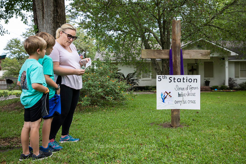 Mallory Anderson, right, reads a reflection to sons Ames, 6, and Cooper, 8, as they visit the fifth station in the Goodwood neighborhood. The Andersons attend Our Lady of Mercy Catholic Church. With churches closed because of COVID-19 many neighborhoods in the Baton Rouge area have organized Stations of the Cross for Good Friday. Marked with simple, homemade signs people can view and pray by car, bike, golf cart or on foot the stations displayed in area front yards.