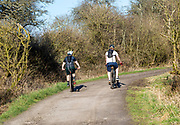 Two people cycling up a track, Yatesbury, Wiltshire, England, UK