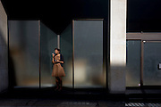A women office worker in her 20s take a cigarette-break outside her place of work's steps in London's west end.