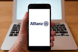Using iPhone smartphone to display logo of Allianz ; a European financial services company headquartered in Munich, Germany