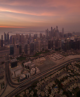 Aerial view of the Palm Jumeirah in background of the towers of Dubai at sunset, U.A.E.