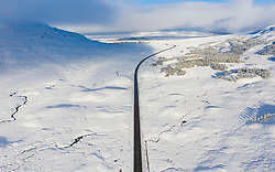 Aerial view of A82 road crossing Rannoch Moor covered in snow during winter, Highlands,Scotland, UK