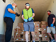 29 MAY 2020 - DES MOINES, IOWA: Workers unload boxes of produce at a produce distribution in a mall parking lot in Des Moines. The Des Moines Area Religious Council (DMARC) and Capitol City Fruit from Norwalk, IA, gave away 1,800 boxes of fresh produce with a mix of vegetables and fruit. The boxes contain enough produce to feed a family of four for a week. The produce was provided by the USDA Farmers to a Families food program. Because of the COVID-19 pandemic, the unemployment rate in Iowa hit 10.2% in May, the highest unemployment rate ever recorded in Iowa and food insecurity in Iowa is impacting communities throughout the state.          PHOTO BY JACK KURTZ