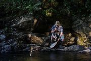 """With uneven footing on a steep bank of the Ompompanoosuc River, James Taylor tries to bring a trout into his net in Thetford, Vt., Thursday, June 24, 2021. """"I just find this the most calming thing,"""" said Taylor who lost the fish off his barbless hook. """"Just being here drops your blood pressure."""" (Valley News - James M. Patterson) Copyright Valley News. May not be reprinted or used online without permission. Send requests to permission@vnews.com."""