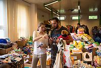 DEU, Deutschland, Germany, Berlin, 17.08.2015: Eine freiwillige Helferin assistiert einem Flüchtling bei der Wahl einer Zahnbürste in der Kleiderkammer der kurzfristig eingerichteten Notunterkunft im Berliner Stadtteil Karlshorst. Die vom DRK betriebene Erstaufnahmestelle in der Köpenicker Allee soll die Zentrale Aufnahmeeinrichtung für Asylbewerber der LaGeSo in Moabit entlasten.