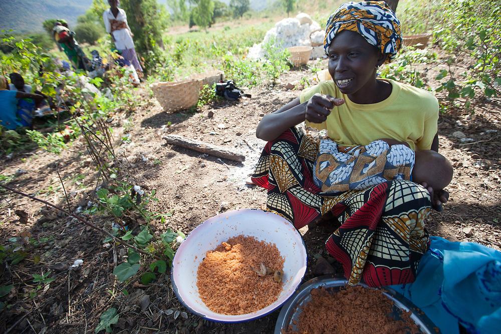 Fatoumata Diallo with a baby, eats lunch in a cotton field