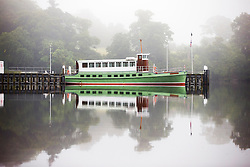 © Licensed to London News Pictures. 14/09/2016. Pooley Bridge UK. Picture shows the Ullswater Steamer sitting on the still water of Ullswater Lake in the morning mist at Pooley Bridge this morning. After last nights thunderstorms in the north of England Cumbria woke to a calm but misty morning. Photo credit: Andrew McCaren/LNP