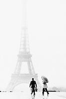 Paris, France --- Man and Woman Walking near Eiffel Tower --- Image by © Owen Franken